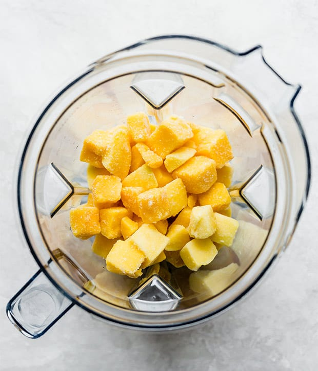 A blender full of frozen mango chunks in preparation for making mango sorbet.
