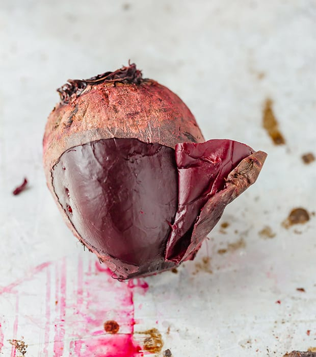 A cooked beet with some of the skin pulling off.