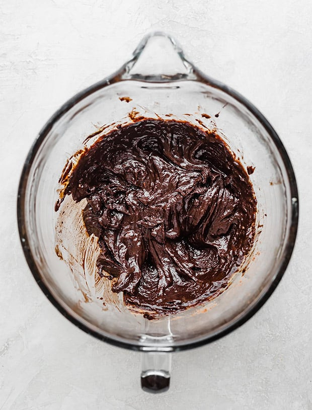 A glass bowl with brownie cookie batter.