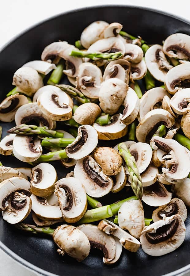 A close up photo of raw mushrooms and asparagus in a black skillet, in preparation to making goat cheese pasta.