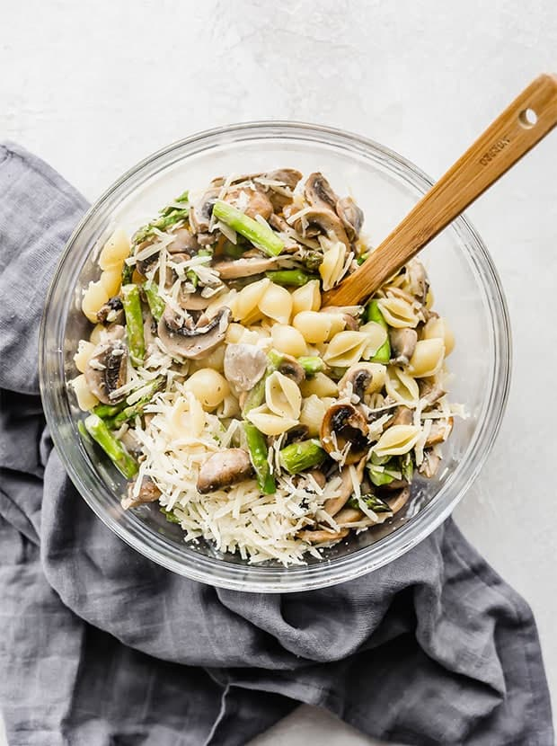 A glass bowl with pasta shells, parmesan, asparagus, and mushrooms in it.