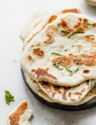 Naan bread on a plate with a small garnish of chopped cilantro.