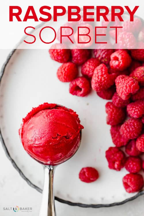 An ice cream scooper with a scoop of raspberry sorbet towards the left of the image, and a pile of red raspberries to the right of the scooper.