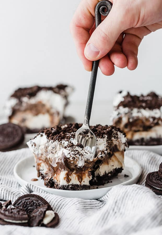 A fork digging into a slice of Oreo Ice Cream Cake.