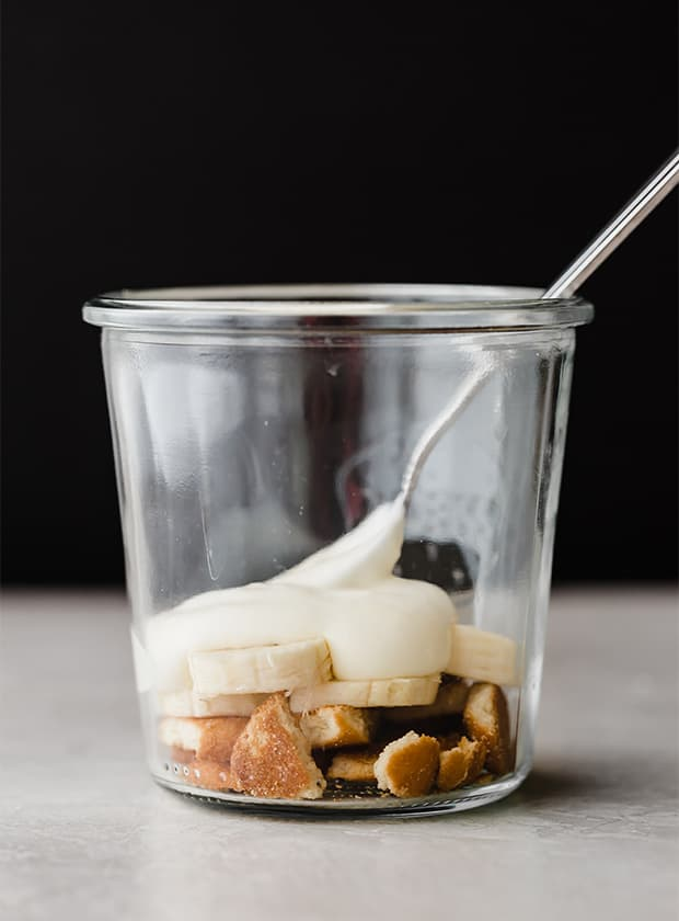 A glass jar with a bottom layer of crushed Nilla wafers, sliced bananas, and a dollop of vanilla pudding.