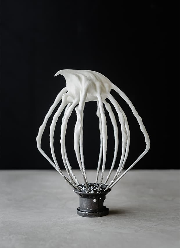 A wire whisk with freshly whipped cream on the whisk.