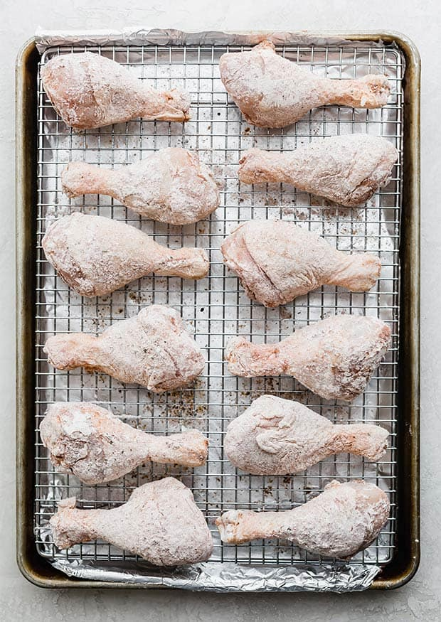 Twelve chicken drumsticks on a cooling rack topped baking sheet prior to being cooked.