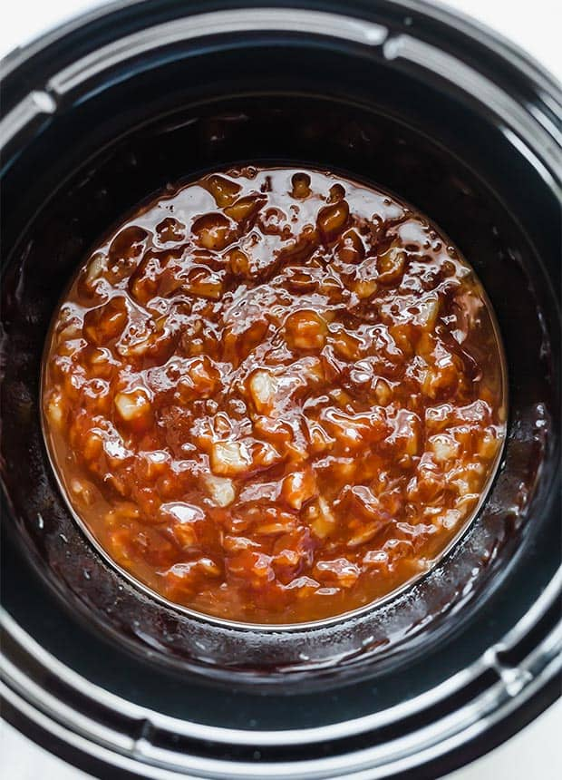 A slow cooker full of barbecue sauce mixed with crushed pineapple.