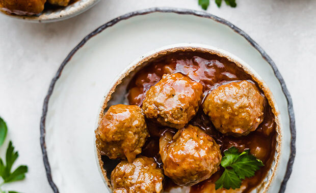 A bowl full of white rice topped with crock pot BBQ pineapple meatballs.