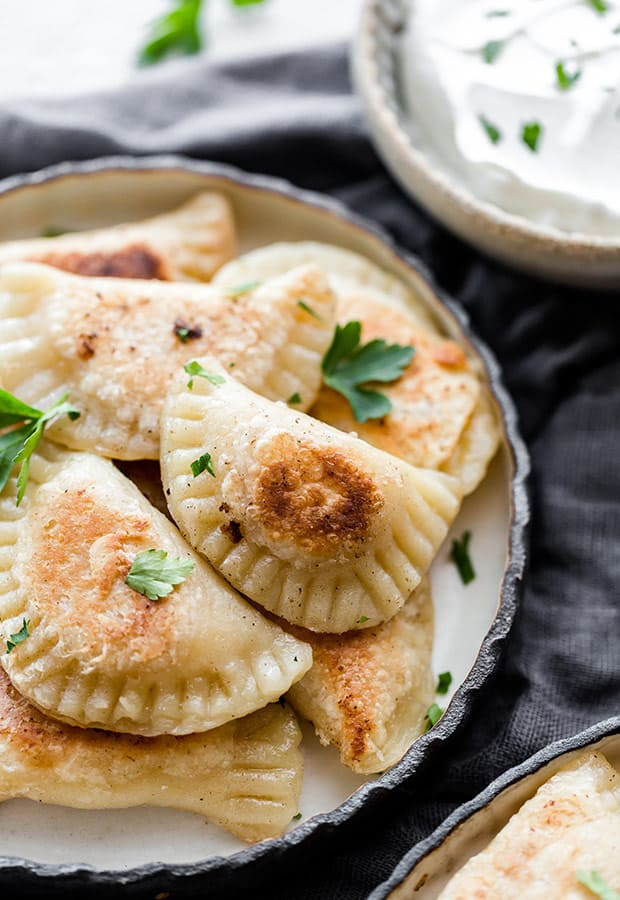 Close up photo of a plate full of homemade pierogies with a bowl of sour cream in the background.