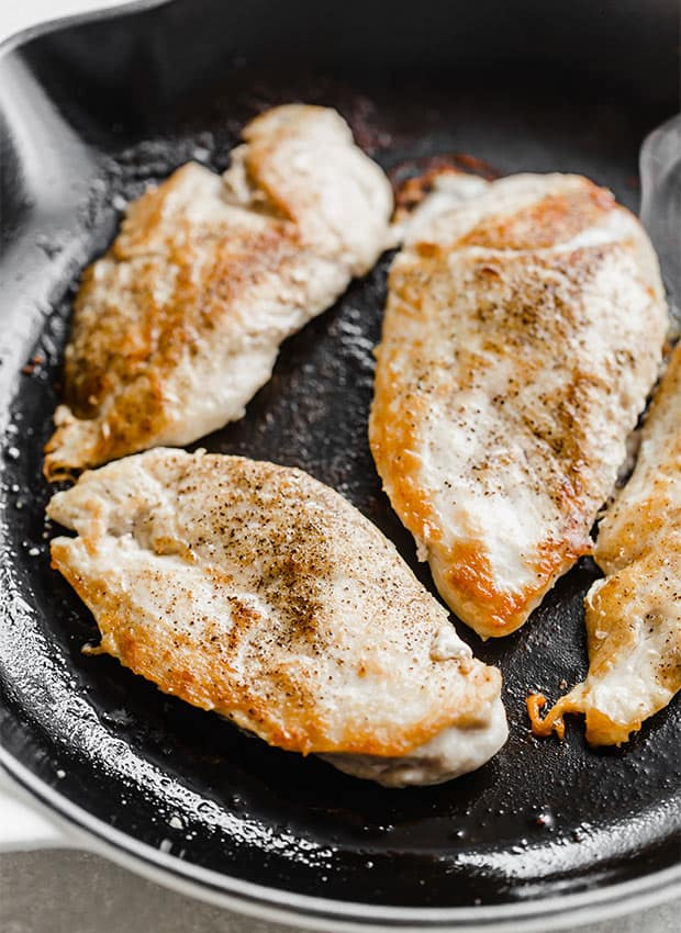 A skillet with 4 seared chicken breasts.