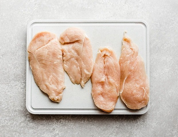 A white cutting board with 4 chicken breast halves on the board.