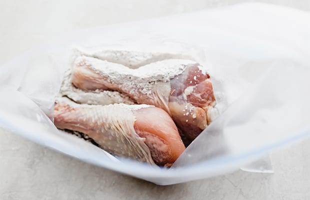 Two raw chicken drumsticks in a ziplock bag.