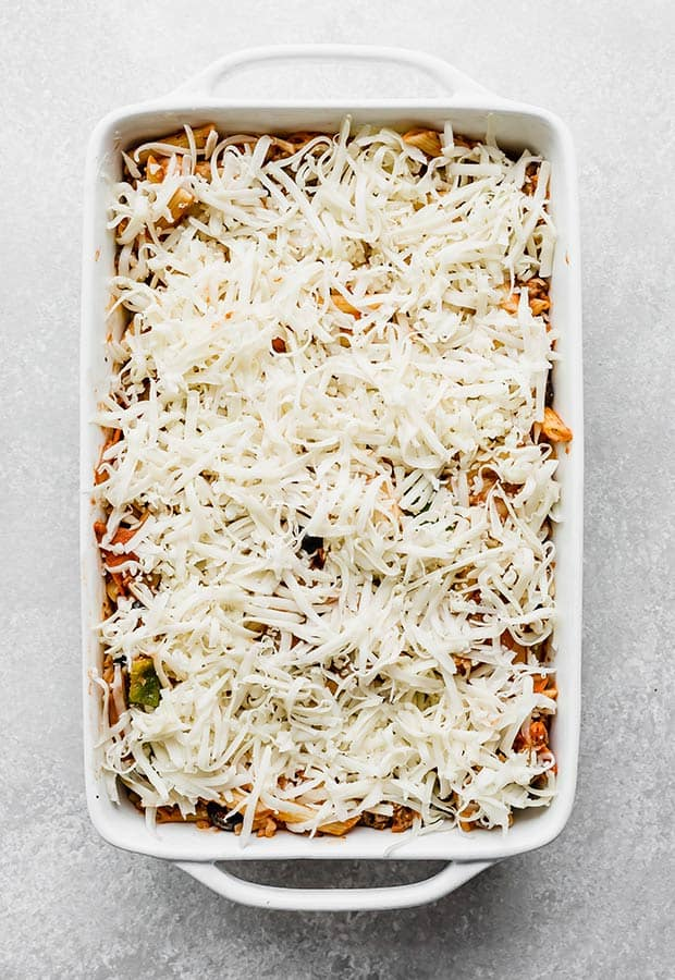 A white casserole dish full of pizza casserole and topped with shredded mozzarella cheese.