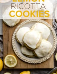 A plate on a wooden cutting board, full of lemon ricotta cookies.