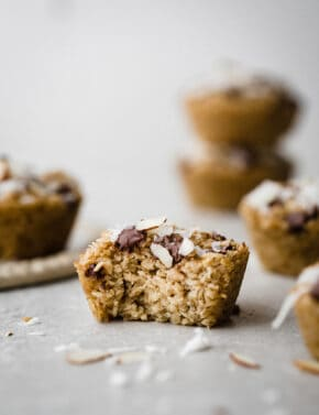 A single baked oatmeal cup with a bite taken out of it, with shredded coconut surround the oatmeal cup.
