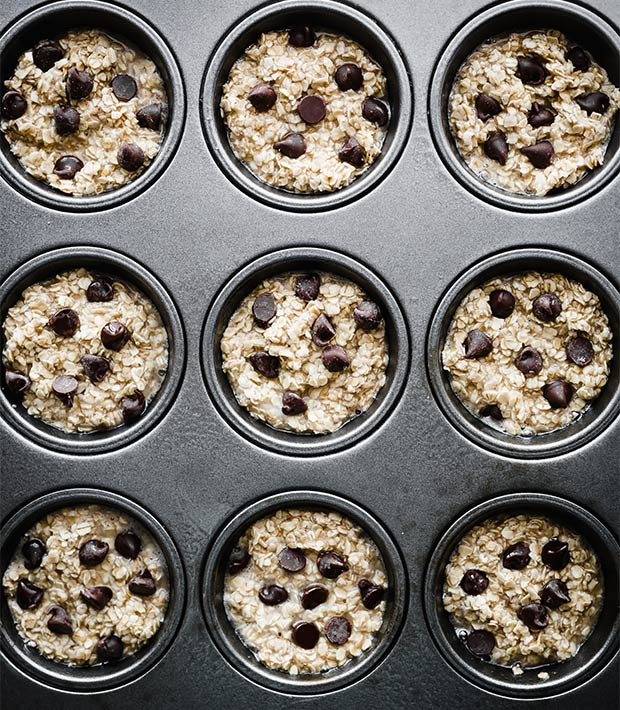 A muffin tin filled with breakfast oatmeal cups batter and topped with chocolate chips.