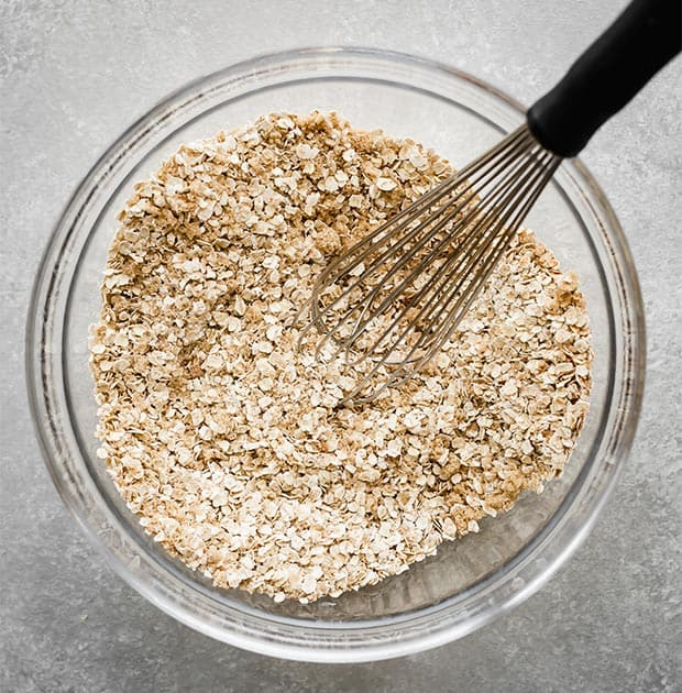 A glass bowl with quick cooking oats, sugar, and other dry ingredients for making baked oatmeal cups.