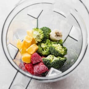 A vitamix blender full of raw broccoli, strawberries, mango, and frozen banana in preparation to make a broccoli smoothie.
