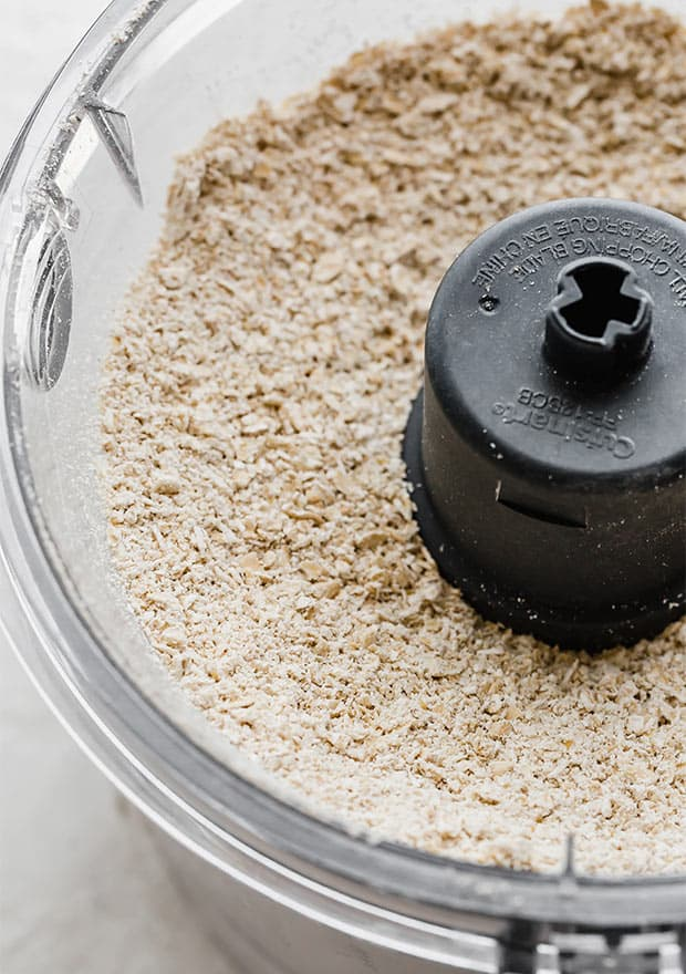 A food processor with ground old fashioned oats, making homemade oat flour.