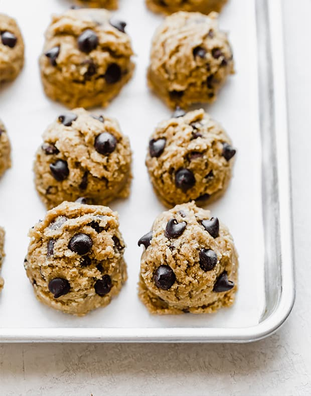 A baking sheet with balls of Brown Butter Chocolate Chip Cookie dough batter.