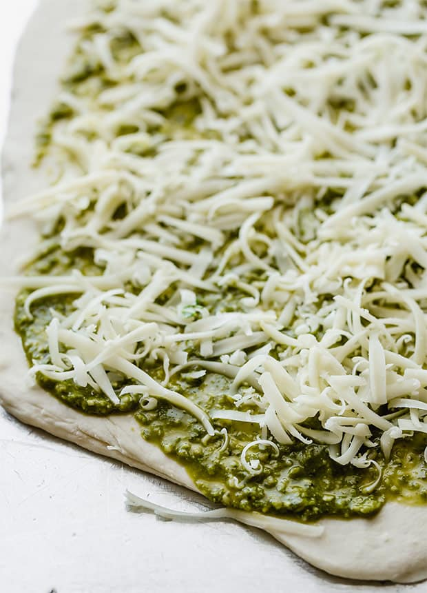 Uncooked pizza dough with basil pesto and shredded mozzarella.