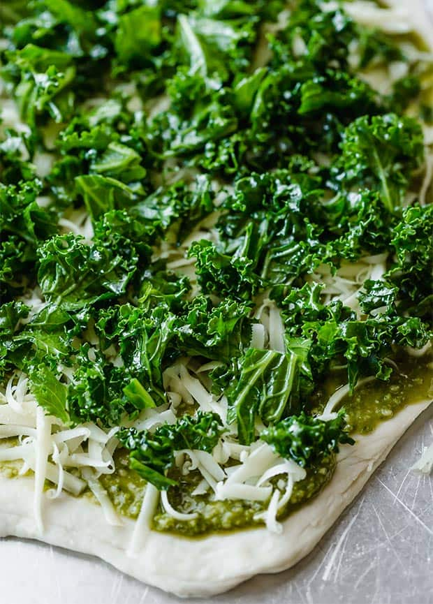 Freshly chopped kale over top of a pizza dough crust, pesto, and mozzarella.