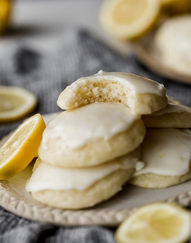 A lemon ricotta cookie on a pile of cookies, with a bite taken out of it.