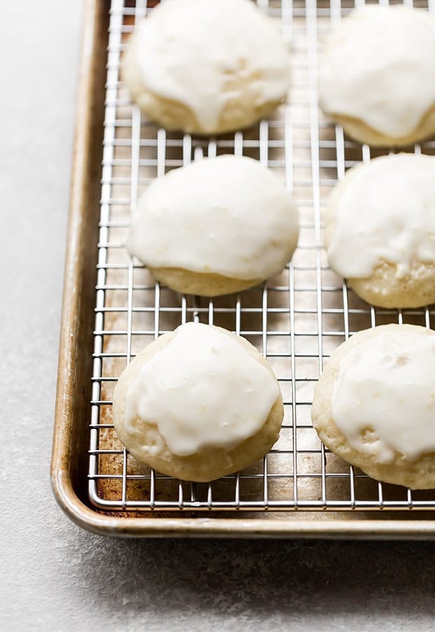 Lemon ricotta cookies on a cooling rack nestled in a baking sheet.