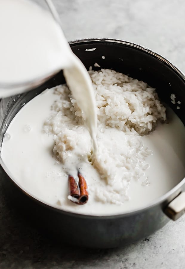 A saucepan with rice and a cinnamon stick in it and milk being poured over the rice for making Mexican rice pudding.