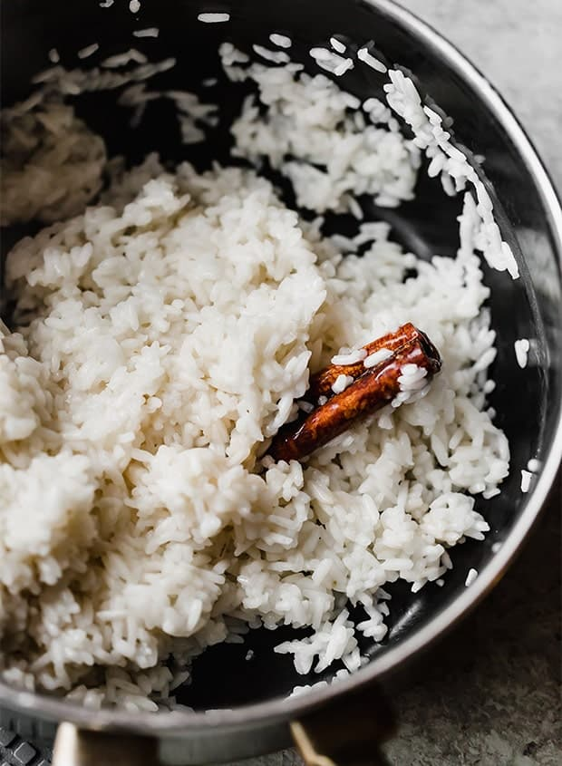 A close up photo of partially cooked rice in a saucepan with a cinnamon stick buried beneath the rice.