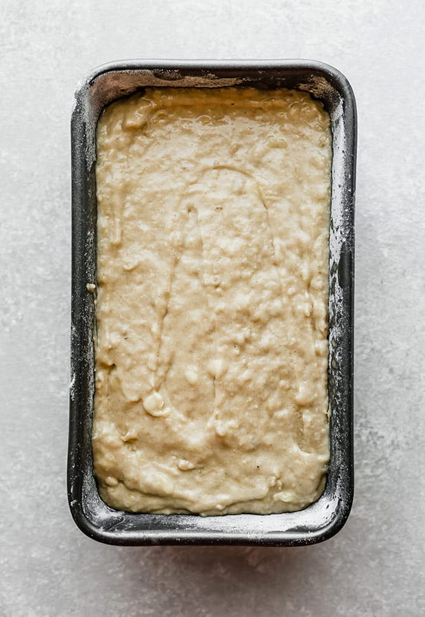 A bread loaf pan full of banana bread batter.