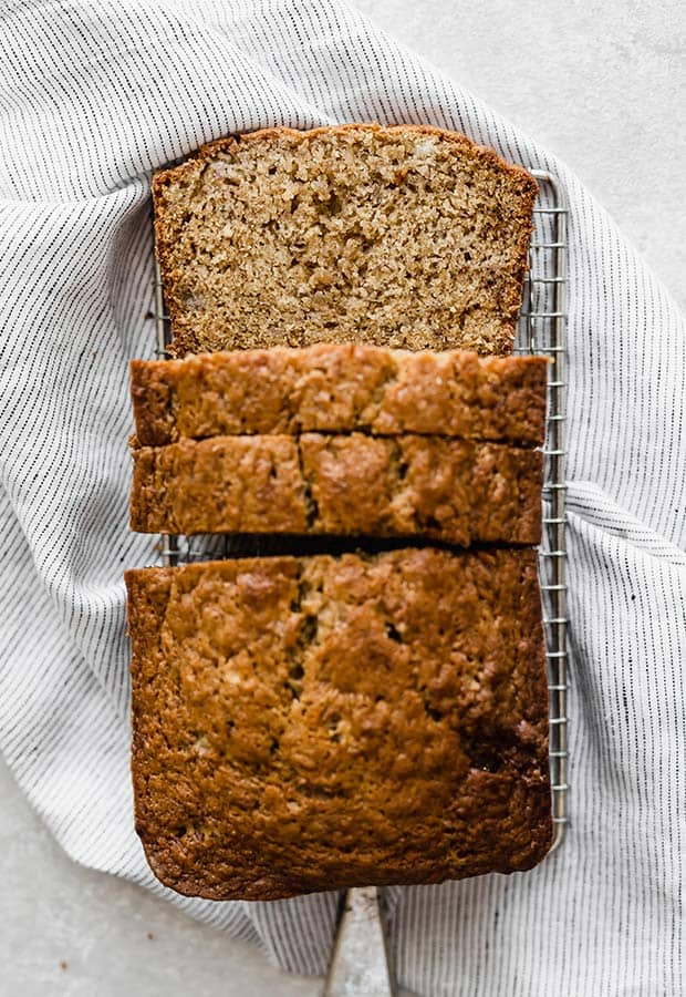 A loaf of banana bread on a small cooling rack, with 3 slices cut, one slice laying flat so that you can see the inside of the loaf.