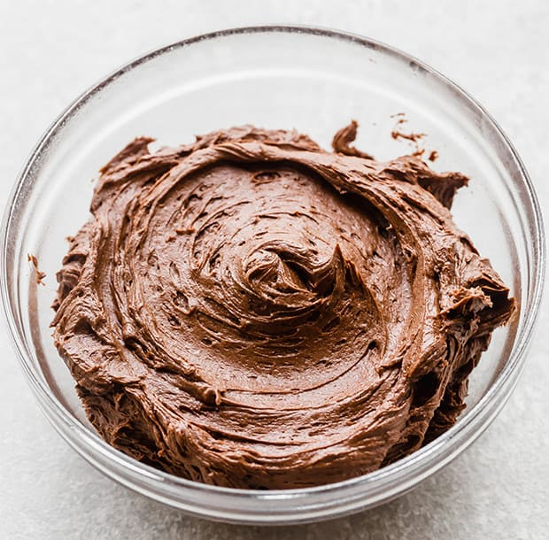 A glass bowl full of Chocolate Buttercream Frosting.