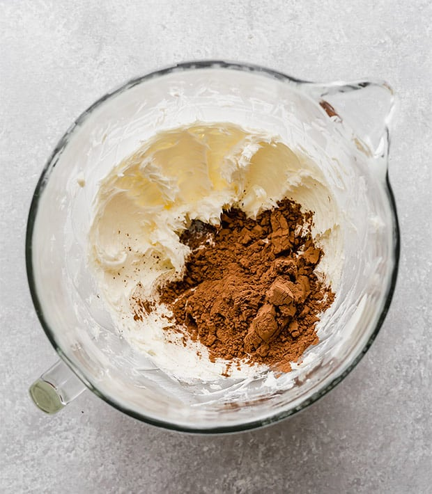 A glass bowl with creamed butter and cocoa powder in the bowl, in preparation to making a delicious chocolate buttercream frosting recipe.