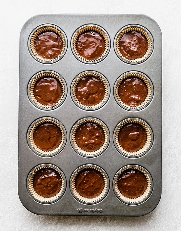 A cupcake pan lined with tan cupcake liners and each cupcake half full with chocolate cupcake batter.