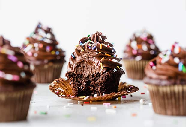 The best chocolate cupcake topped with chocolate buttercream frosting and colorful sprinkles, with a large bite taken out of the cupcake.