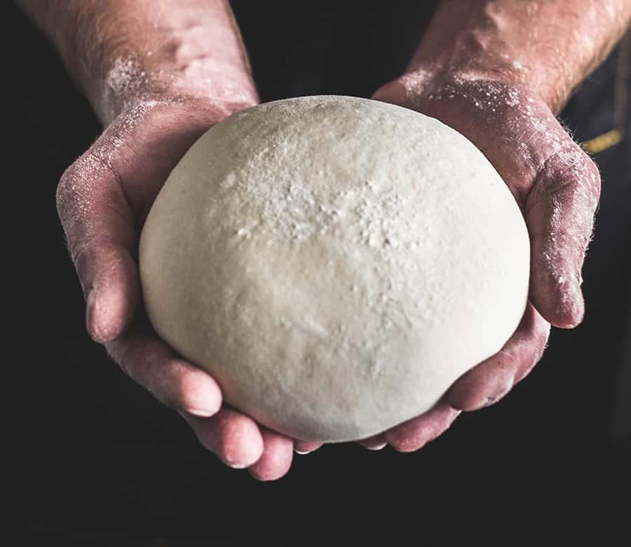 A mans hands holding a ball of dough.
