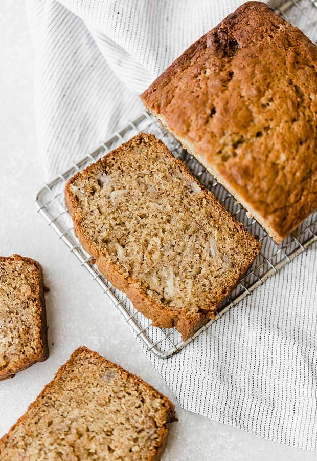 A loaf of easy banana bread on a cooling rack with a slices of the bread around the loaf.