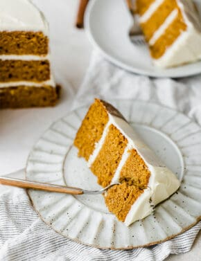 A slice of pumpkin layer cake on a plate with a fork cutting into the cake.