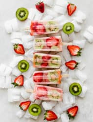 Five kiwi strawberry popsicles on top of a pile of ice cubes.