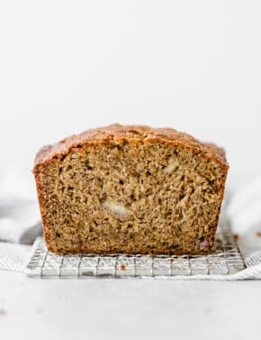 A moist banana bread loaf sitting on a small wire rack.