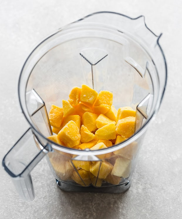 A blender full of frozen mango chunks.