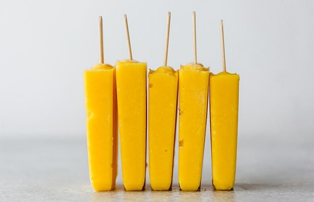 Five pineapple mango popsicles standing on its ends lined up by each other.