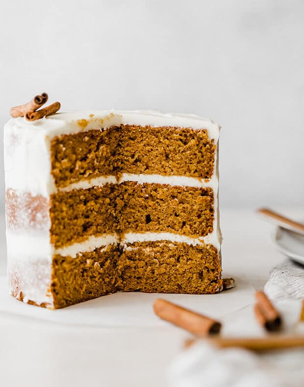 A three layered pumpkin cake with cream cheese frosting, with a big slice cut out of the cake showcasing the inside layers.