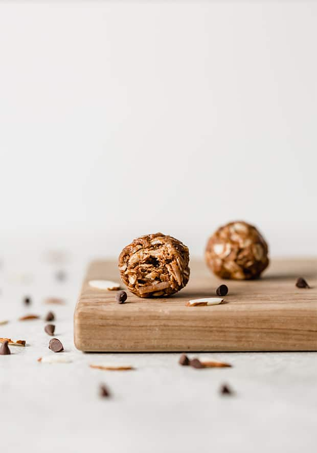 A healthy almond joy bite sitting on a wooden board, with a bite taken out of it.