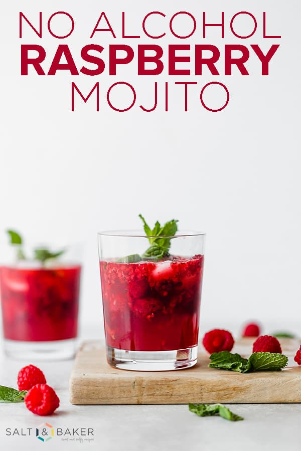 A glass cup on a wooden cutting board full of raspberry mojito mocktail with scattered raspberries and mint leaves near the cup.