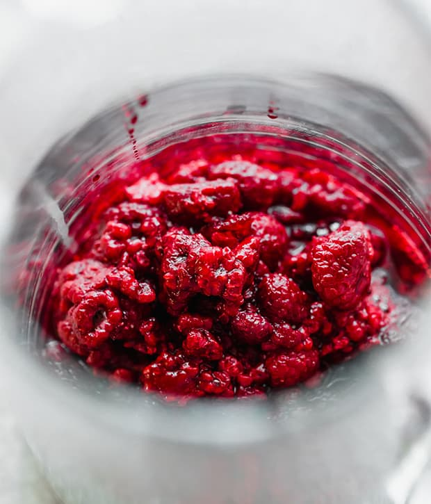A close up photo of a glass pitcher full of thawed previously frozen raspberries in the pitcher.