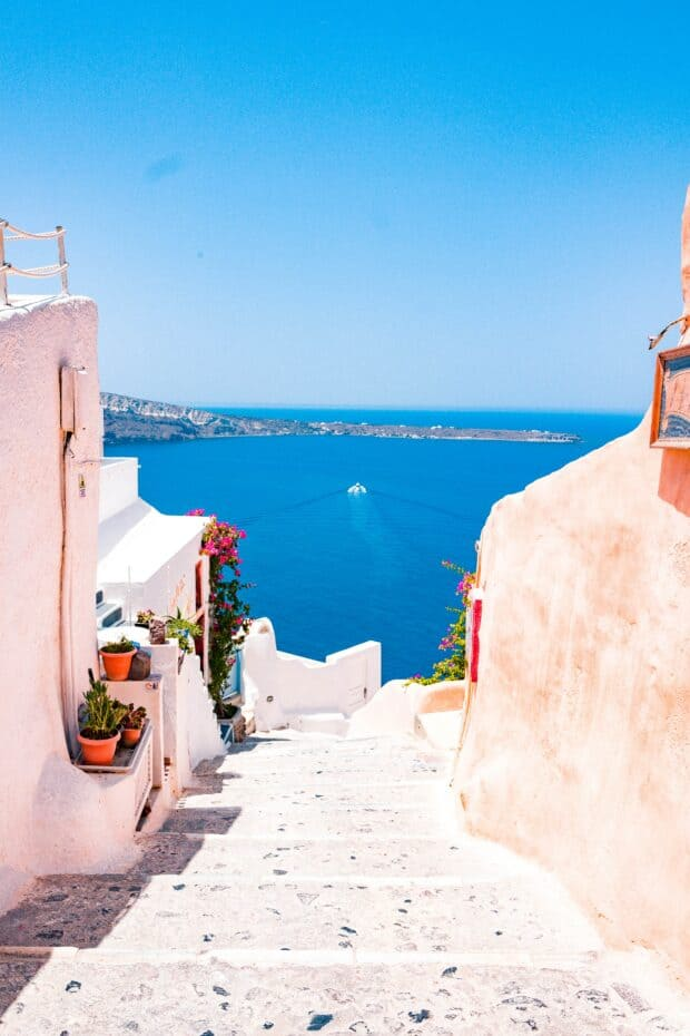 A photo of Santorini Greece with the bright blue ocean in the background.