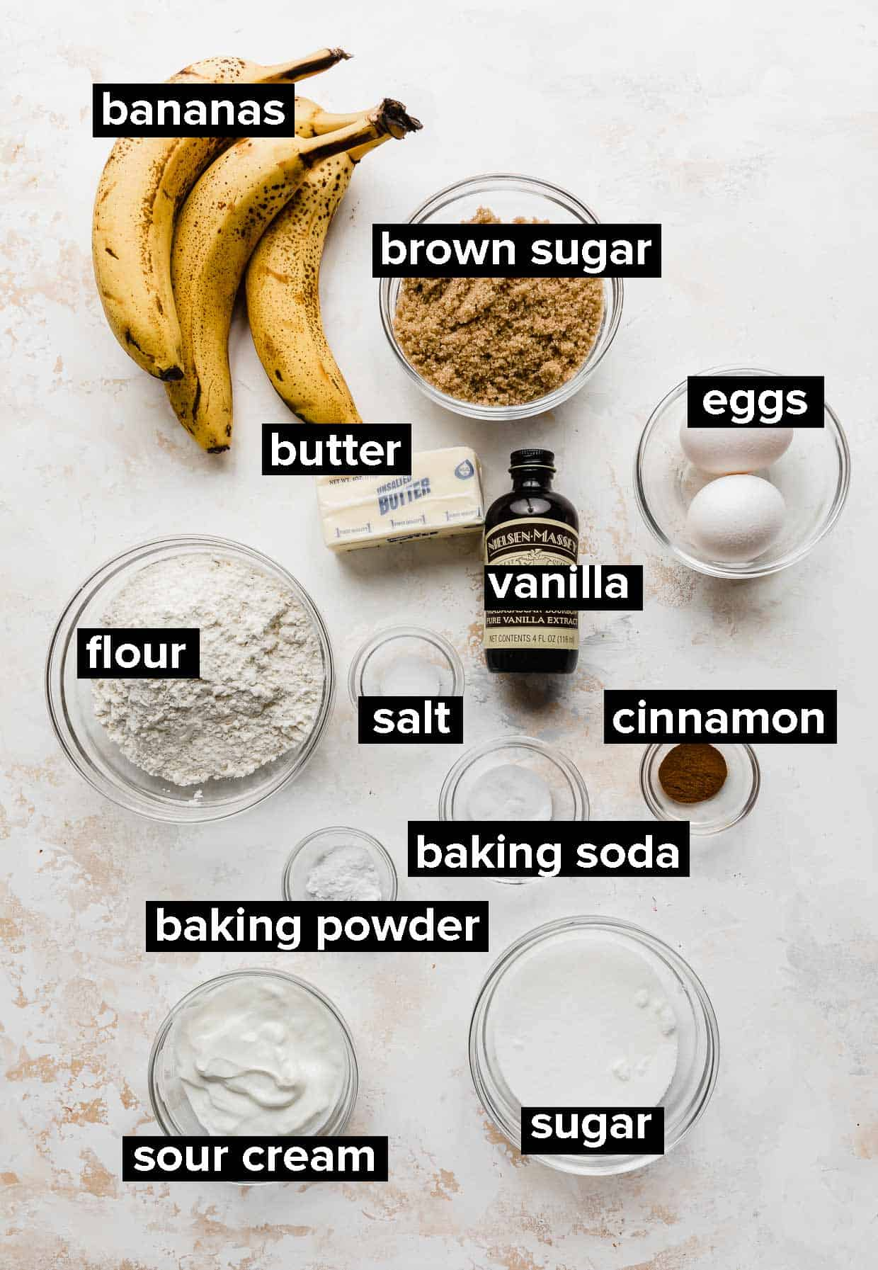 Ingredients used to make moist banana bread spread out on a cream and white textured background.